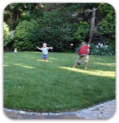 Picture of children playing in green lawn with patio and flowering garden